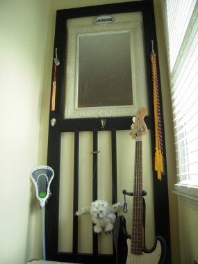 A once slammin screen door given new life on a bedroom wall...embellished with a few practical hooks and a mirror...