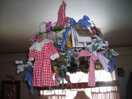 chandelier made from wire fencing, ripped blue and red ginham, tied on insulators, tiny vintage kids books and favorite doll dress, hangs in my livingroom!