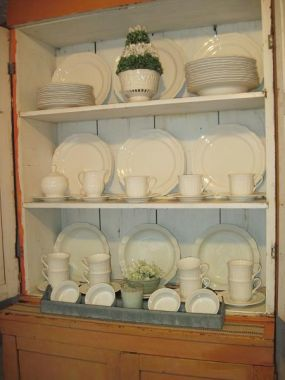 I used this old rusty chicken feeder (bottom row) to hold some smaller pieces of wedding china and a pretty green candle.