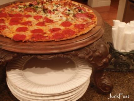A super large wood trivet mounted to cast iron stove legs holds a large pizza...or cheese & crackers!