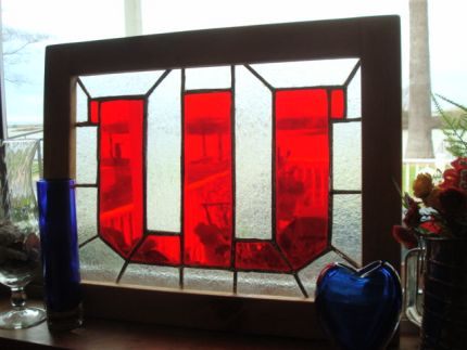 This window is one of a kind, made from red glass that was left over from another project. The clear is glue glass and has a vine pattern and raised texture. To make the pattern, I traced a large W letter stencil and then broke the background up into cutable pieces. The frame I made from wood scraps from my workshop.