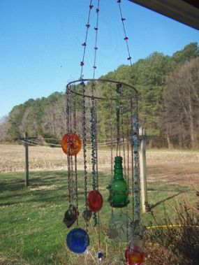 I used the metal hoop as the center of it, used a necklace to hand the whole piece from a hook on my porch, and of course the parts that are hanging are made from necklaces, beads and baubles. This is how my suncatcher mini-chandelier loks right now.  Its hanging on my porch, and now that were actually getting some sun, it looks wonderful.
