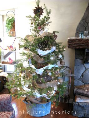 The real cut tree was placed in an old tub to emulate as if it was a live variety. A great junk touch that removes the need for a traditional tree skirt! Garland is both burlap and white torn sheets.