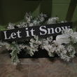 A vintage black painted tool trug filled with branches covered with faux snow, a white dove (.10) and a Let it Snow sign (2.00).