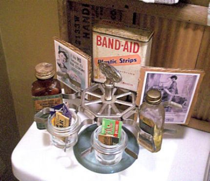 A rubber stamp holder (a flea market steal for $1!!) repurposed to hold old medicine bottles and band-aid tin box, vintage tissue ads, and my favorite find: old inkwells displaying vintage razor blades.