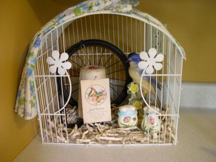 Heres a fun summer vignette. I started with an old bird cage. I cut out some of the front with wire cutters and sprayed it white. I added an old string holder, bluebird, postcard, wheel, shredded music paper, (my fav), and vintage S&P shakers. I topped it off with a vintage apron to tie all the colors together.