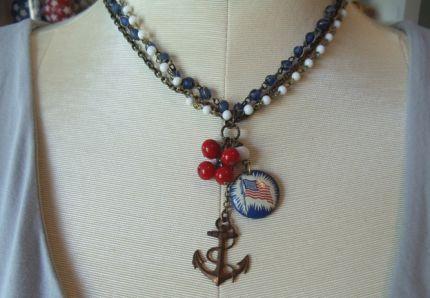 This beautiful and colorful necklace is an assemblage of antiqued brass  chain, vintage milk glass bead chain, and vintage blue glass bead chain.  Hanging from the chain is a wonderful collection of vintage trinkets, a  cherry red glass bead cluster, vintage flag pin back, and a brass  anchor charm. The chain measures 15 and the charms hang 3 off the  chains.