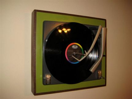 People often throw out old non-working record players.  I rescued a couple of them and made frames for the turntables and gave them easel backs so they hang on the wall or stand on their own.  I made gifts of them to my sons displaying vintage vinyls of their favorite musicians.