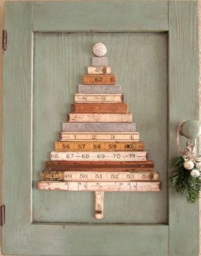 Vintage folding rulers + tattered old cabinet door = Christmas tree wall art.