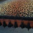 Leopard print with black fringe detailing on my desk chair I found in the dumpster years ago.