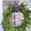 A simple green wreath hanging from a shepards hook.