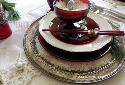 The Royal Ruby Reds mixed with clear glass, simple white dishes, and vintage silver trays as chargers sets the scene.