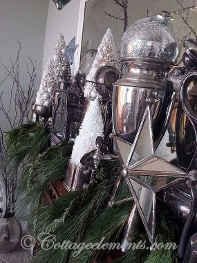 My front room, or parlor as you will, has an array of my silver plated collection of different serving pieces displayed on my mantel. With some trees and extra bling, I have created a little winter wonderland.