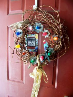Vintage bulbs and their reflectors get a new life on a wreath made from grapevine from my backyard! I placed a little bird and a wooden hand to add some whimsical touches.  I added a big gaudy gold bow and it welcomes visitors to my cottage!